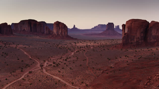 swooping drone shot over monument valley at sunset - butte rocky outcrop stock videos and b-roll footage