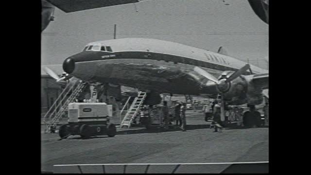 stockvideo's en b-roll-footage met sydney airport row of international nation flags / qantas super constellation plane on tarmac ground crew and refueling / nsw premier joe cahill... - start  en landingsbaan