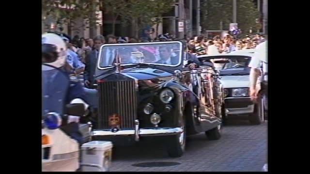 vídeos y material grabado en eventos de stock de city -– police run alongside motorcade / crowds watch from office buildings / motorcade – charles and diana in open top car / parliament house –diana... - 1983