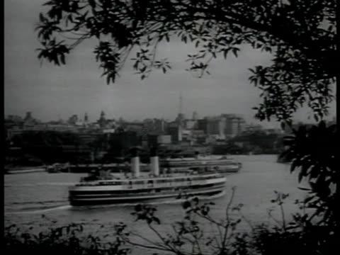 sydney harbor w/ passenger ships passing. sydney harbor w/ motorboat on water, sydney harbor bridge bg . - passagierschiff stock-videos und b-roll-filmmaterial