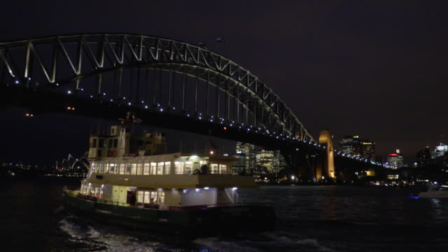 sydney harbour bridge with passing ferry at night - steve munro stock videos & royalty-free footage
