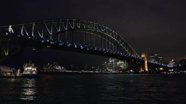 sydney harbour bridge with waiting ferry at night - steve munro stock videos & royalty-free footage