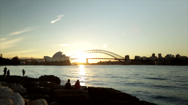 ws sydney harbour opera house at end of bennelong point unidentifiable people standing sitting on waterfront rocks fg bright sun behind harbour... - bennelong point stock videos and b-roll footage