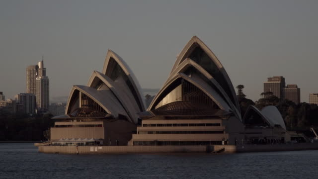 ws sydney opera house on bennelong point in sydney harbour sunlight reflecting off walls city highrise buildings skyscrapers bg - bennelong point stock videos and b-roll footage