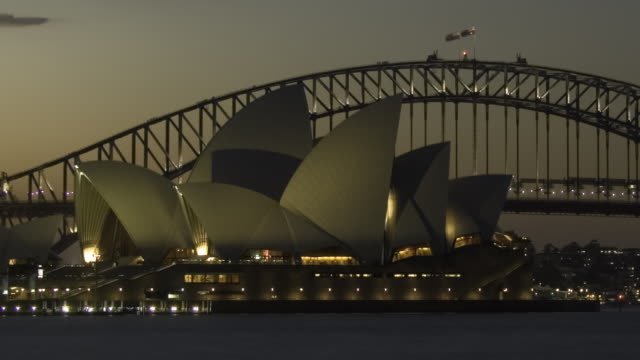 T/L WS PAN Sydney Opera House, Sydney Harbour Bridge, and boats passing in harbor as dusk turns to night/ Sydney, Australia