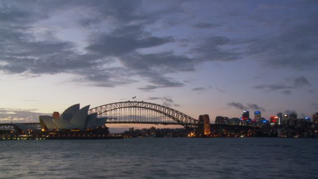 t/l ws sydney opera house with sydney harbour bridge at dusk / sydney, new south wales,  australia - sydney video stock e b–roll