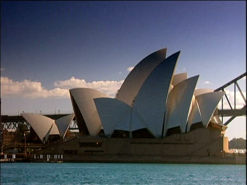 sydney opera house with water in foreground sydney harbour bridge just visible behind - bennelong point stock videos and b-roll footage