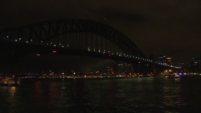 sydney's opera house and harbour bridge plung into darkness to mark earth hour as global landmarks begin dimming their lights to draw attention to... - earth hour stock videos & royalty-free footage