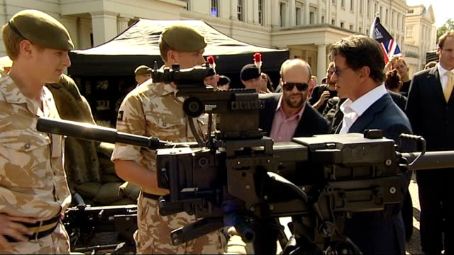 vídeos de stock, filmes e b-roll de sylvester stallone meets british troops stallone along in front of people taking photographs / close up statham / statham and stallone / various of... - sylvester stallone