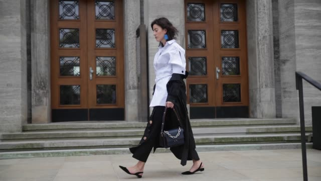 sylvia haghjoo wearing eudon choi black pants and white blouse a black bassike coat navy marni bag blue jw anderson earings paul andrew flat shoes on... - marni stock videos & royalty-free footage