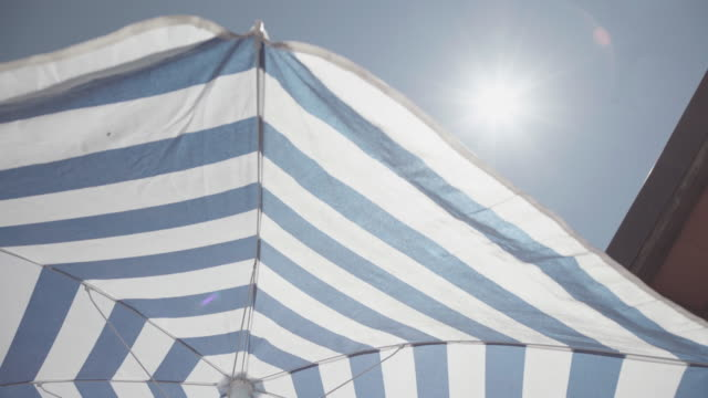 symbols of summer: spinning beach umbrella - beach umbrella stock videos and b-roll footage