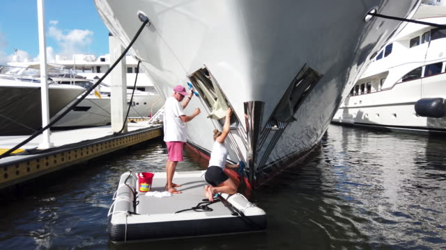 syndey luongo and tim laughridge scrub the bow of lady victory a 120 foot feadship yacht in preparation for display at the 60th annual fort... - yacht stock videos & royalty-free footage