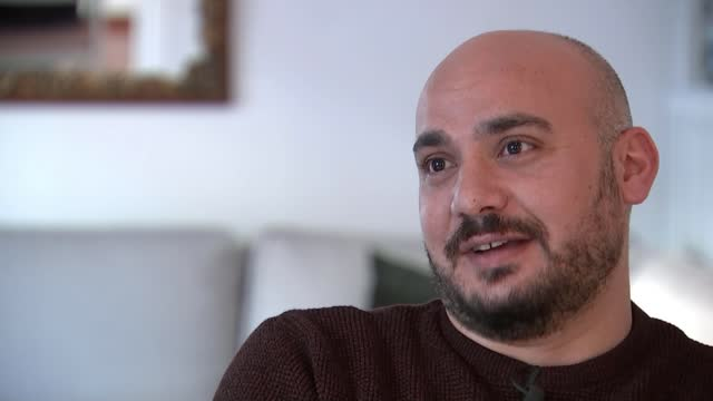 syria 10 years of war: refugee reflects on civil war anniversary; greece: athens: int abdo shikhi interview sot cutaway shikhi's wife renee listening - war and conflict video stock e b–roll