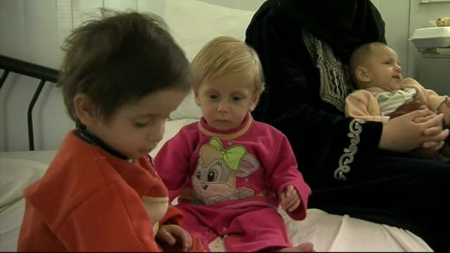 special report on zaatari refugee camp jordan zaatari refugee camp int veiled woman sitting holding baby next to to two children on bed in hospital... - camp bed stock videos & royalty-free footage