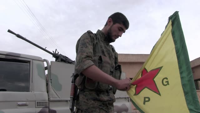 syria. hasakah, 12th october, 2014. a kurdish fighter folds the official flag of the kurdish people's protection units ypg in a military base in al... - people's protection units stock videos & royalty-free footage