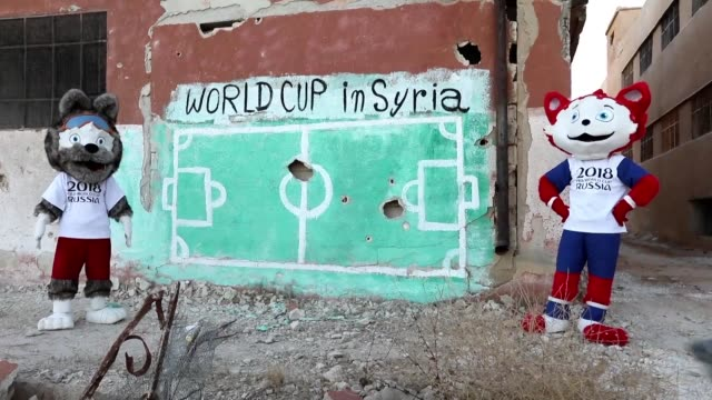Syrian activists in the northwestern Syrian town of Binnish wearing Russia 2018 World Cup mascots costumes take part in a performance to protest...