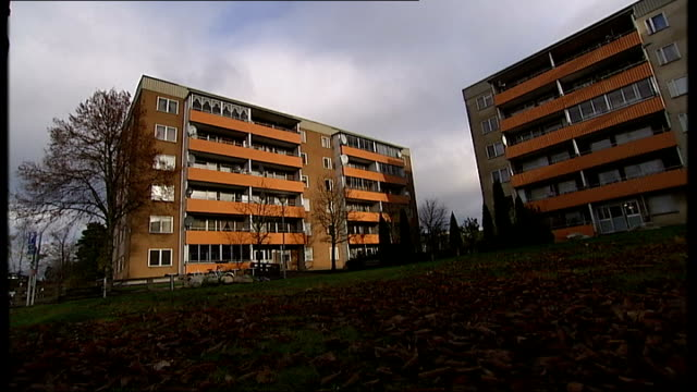 syrian asylum seekers in stockholm sodertoelje street puddle with flats in background / apartment blocks / empty children's playground with swings /... - satellit stock videos & royalty-free footage