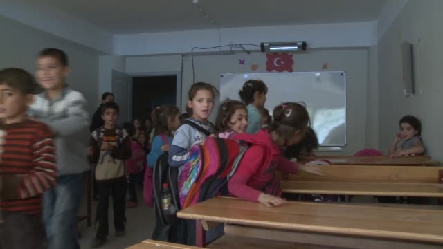 syrian children carrying backpacks enter make-shift classroom in refugee camp in turkey. teacher at head of classroom. - head teacher stock videos & royalty-free footage