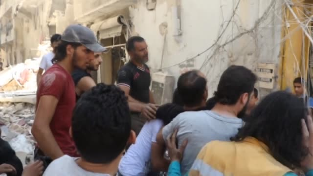 syrian civil defense members and civilians search for survivors in the rubble of buildings destroyed in attacks with naval mine cluster munition... - munition stock-videos und b-roll-filmmaterial