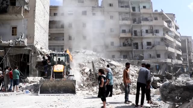 Syrian civil defense members and civilians search for survivors in the rubble of buildings following barrel bomb attacks carried out by Syrian regime...