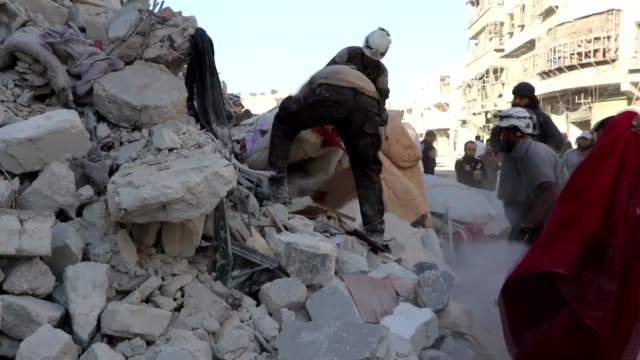 Syrian civil defense members and civilians search for survivors in the rubble of buildings after Russian fighter jets struck alMarja district by...