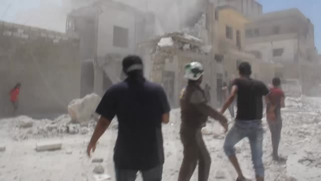 Syrian civil defense members search for survivors in the rubble of buildings destroyed after the Russian airstrikes targeted Idlib Syria on July 20...