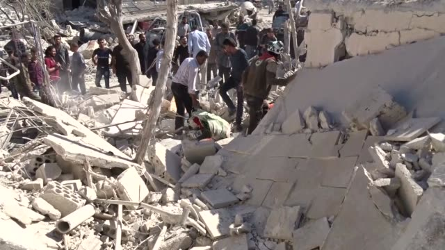 Syrian civil defense team members and civilians carry out search and rescue work after the warcrafts belonging to the Russian Army hit a school in...