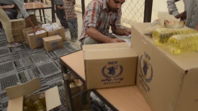 syrian civil war refugees acquire food aid supplies at storage facility in jordanian refugee camp - シリア難民問題点の映像素材/bロール