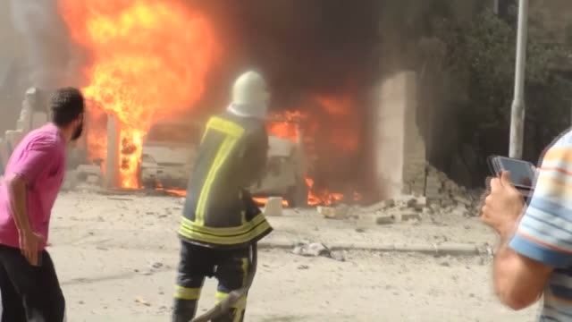 Syrian firefighters try to extinguish a fire at a bakery after it was hit by a barrel bomb dropped by Syrian regime forces in Ansari neighborhood of...