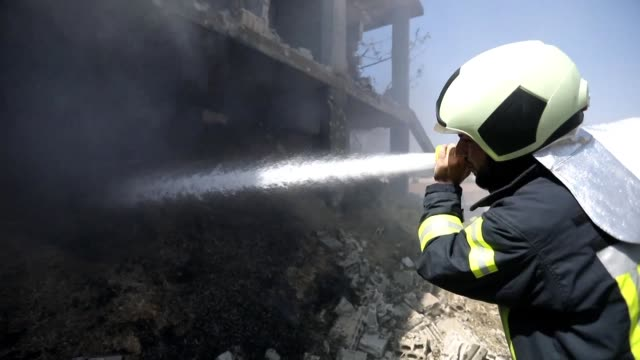 vídeos y material grabado en eventos de stock de syrian firefighters try to put out fires following reported russian airstrikes on the rebel held towns of muhambal and jadraya in syria's idlib... - air raid