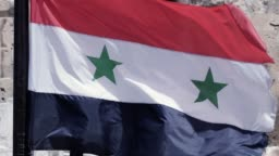 Syrian flag flying because of the wind. We can see an ancient  building in the backgound