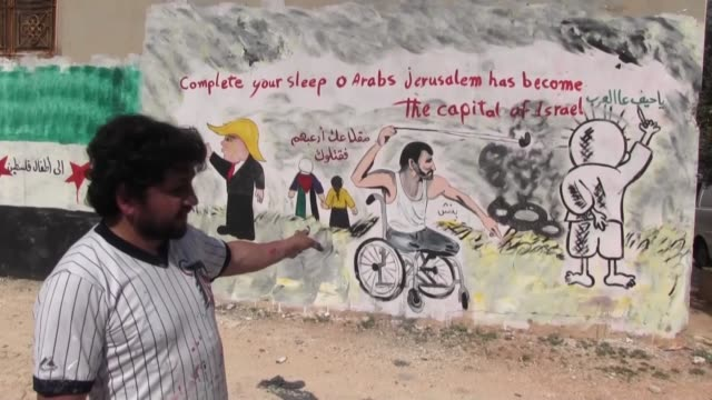 Syrian graffiti artist Aziz alAsmar shows his solidarity with the people of the blockaded Gaza Strip by spraypainting proGaza slogans and images on...