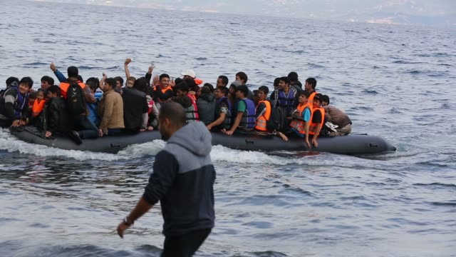 syrian migrants arriving from turkey in an overloaded boat on the greek island of lesvos. - isil konflikt stock-videos und b-roll-filmmaterial
