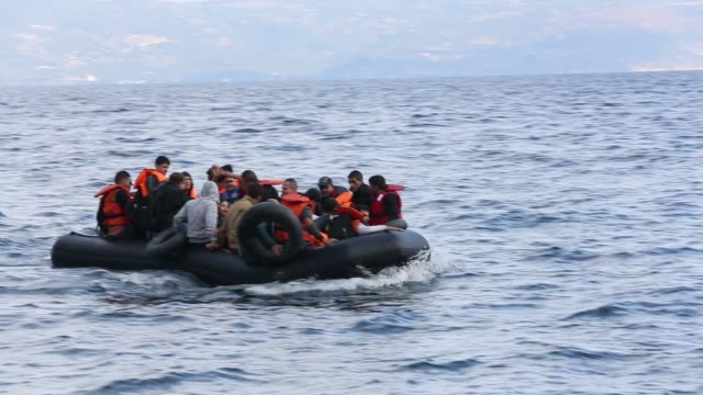 vídeos de stock e filmes b-roll de syrian migrants fleeing the war and escaping to europe, landing on the greek island of lesvos on the north coast at efthalou. up to 4,000 migrants a day are landing on the island and overwhelming the authorities. they are traficked by illegal turkish peopl - barco