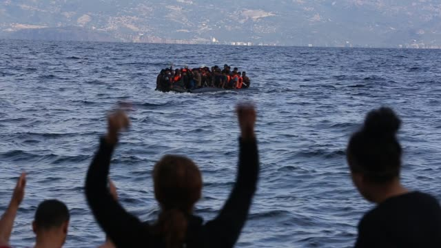 stockvideo's en b-roll-footage met syrian migrants fleeing the war and escaping to europe, landing on the greek island of lesvos on the north coast at efthalou. up to 4,000 migrants a day are landing on the island and overwhelming the authorities. they are traficked by illegal turkish peopl - ontsnappen