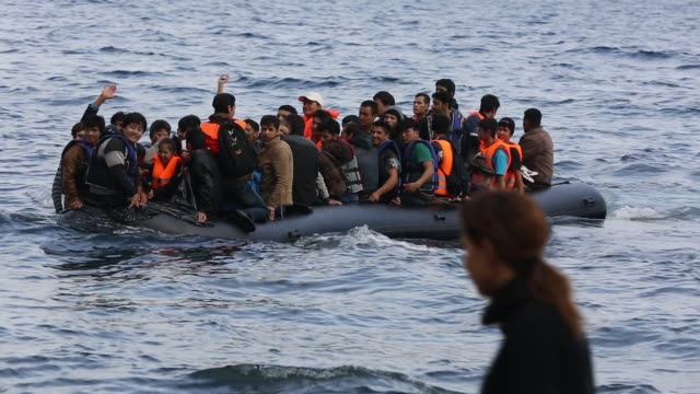 syrian migrants fleeing the war and escaping to europe, landing on the greek island of lesvos on the north coast at efthalou. up to 4,000 migrants a day are landing on the island and overwhelming the authorities. they are traficked by illegal turkish peopl - problem stock-videos und b-roll-filmmaterial