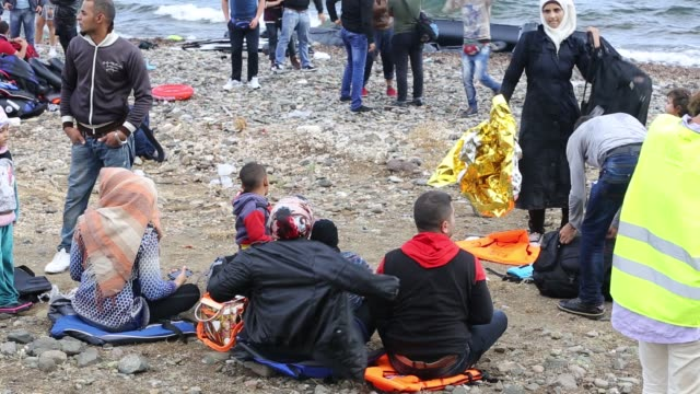 syrian migrants on the beach after they arrived from turkey on the greek island of lesvos. - isil konflikt stock-videos und b-roll-filmmaterial