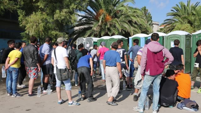 syrian migrants queue for toilets in mytilini on the greek island of lesvos. - isil konflikt stock-videos und b-roll-filmmaterial