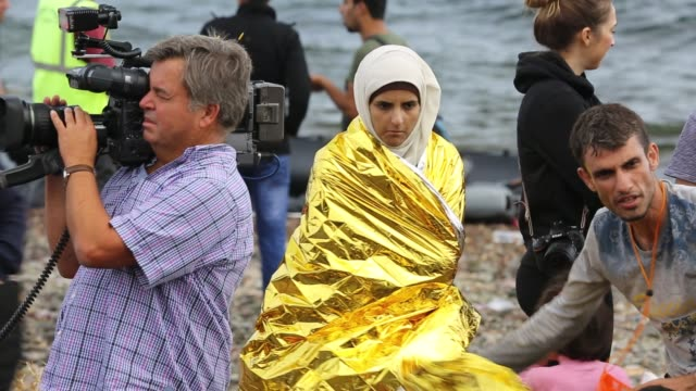 syrian migrants wrapped in insulated blankets to warm them up, after they arrived from turkey on the greek island of lesvos. - middle east stock videos & royalty-free footage