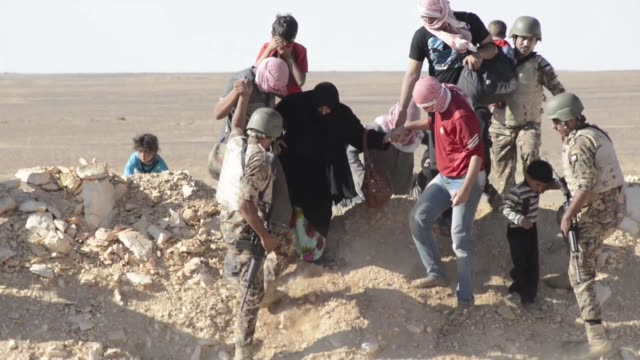 syrian refugees assisted by jordanian soldiers over berm in desert great shot of soldier carrying child older woman helped by friends - シリア難民問題点の映像素材/bロール