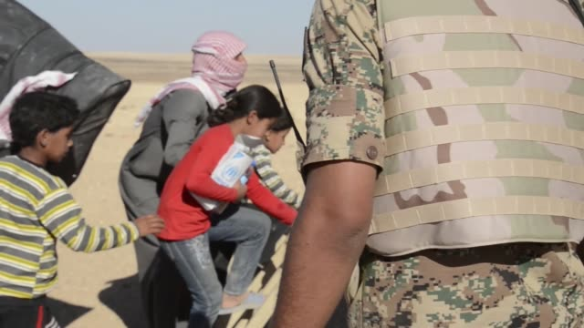 Syrian refugees walk toward Jordanian military truck climb in