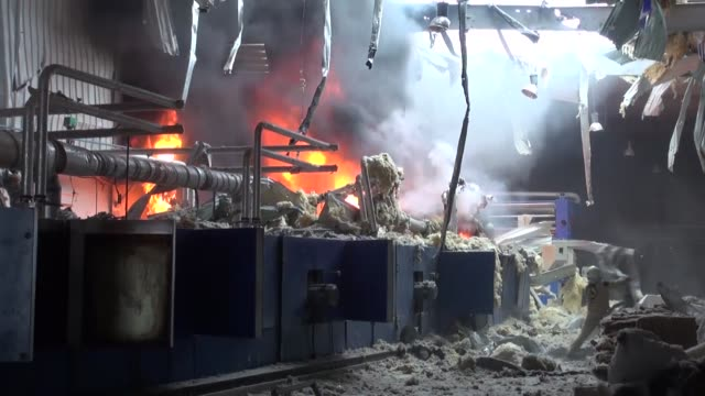 syrian regime forces launch air strike on a fiber factory in hayyan town of aleppo syria on february 25 2015 firefighters try to extinguish the fire... - 武力攻撃点の映像素材/bロール