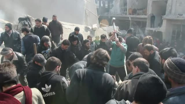 syrian search and rescue team and residents inspect the debris of a destroyed building following an air strike by syrian regime forces in arbin town... - 武力攻撃点の映像素材/bロール
