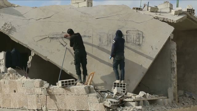 syrian teenagers depict murals on the wreckages of buildings to protest the attacks of syrian regime forces in dareyya district of damascus syria on... - 表す点の映像素材/bロール