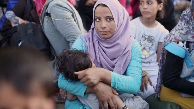 syrian women wait to cross the border with her family after waiting 20 hours on september 2 2015 in idomeni greece several thousand migrant people... - flüchtling stock-videos und b-roll-filmmaterial