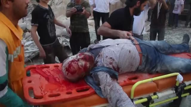 Syrians and rescuers carry wounded people out of collapsed buildings as search and rescue operations continue among the debris of houses following a...