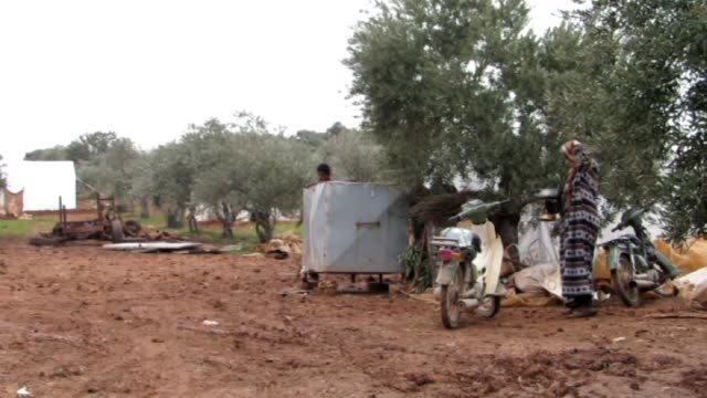 Syrians fled their homes due to the attacks of Assad regime forces try to hold on life under harsh living conditions worsened by heavy rains of...