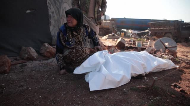 syrians mourn over the bodies of relatives killed after air strikes of the syrian regime and its russian ally hit a camp for the displaced located on... - trauerzeit stock-videos und b-roll-filmmaterial