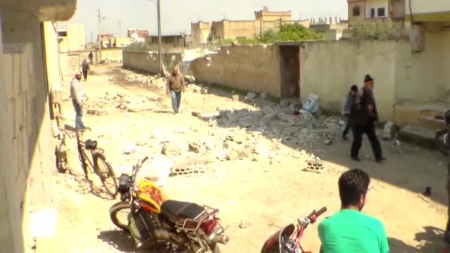 Syrians walk among wreckages of damaged buildings after war crafts belonging to Syrian army carried out airstrikes over residential areas in Houla...