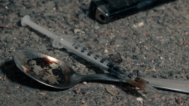 syringe and heroin spoon on a dirty concrete floor - injecting heroin stock videos & royalty-free footage